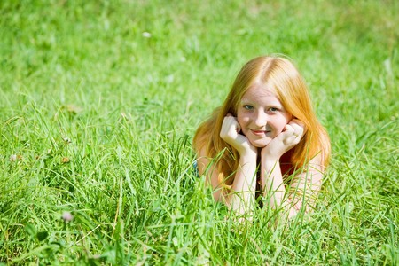 Red-haired teen girl is lying at grass Stock Photo - 7375244