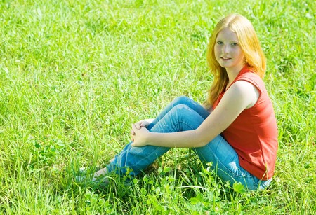 Pretty teenager girl  sitting in meadow grass Stock Photo - 7375240