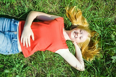 Carroty  teenager girl lying at meadow grass
