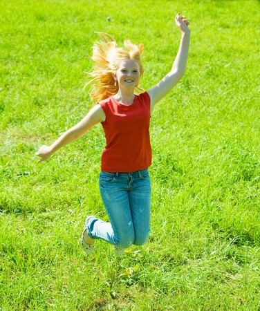 Jumping red-haired teen girl against green grass Stock Photo - 7375236