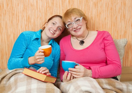 Happy woman and her adult daughter on sofa at home photo