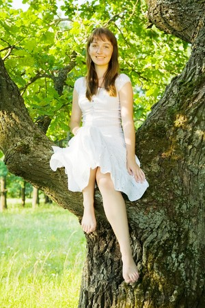 Girl in white sitting on tree against forest photo