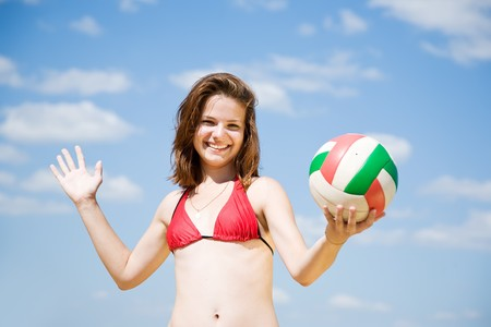 Young girl playing volleyball against blue sky photo
