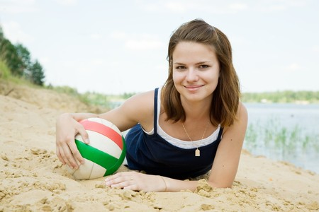Portrait of sporty girl with volleyball on sand beach photo