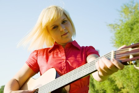 pretty girl playing guitar against blue sky Stock Photo - 7375299
