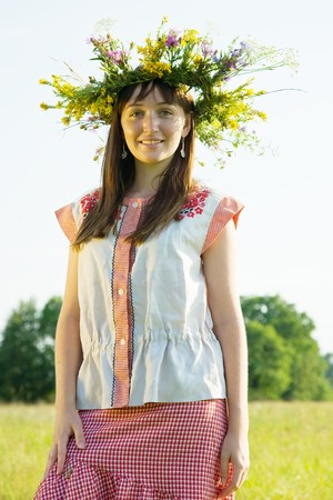 girl in flowers wreath and traditional clothes against nature photo
