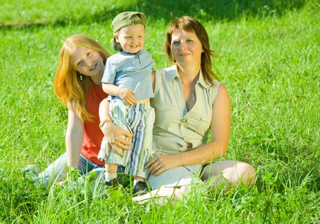 Happy mother with her children  sit in grass  Stock Photo - 7375329