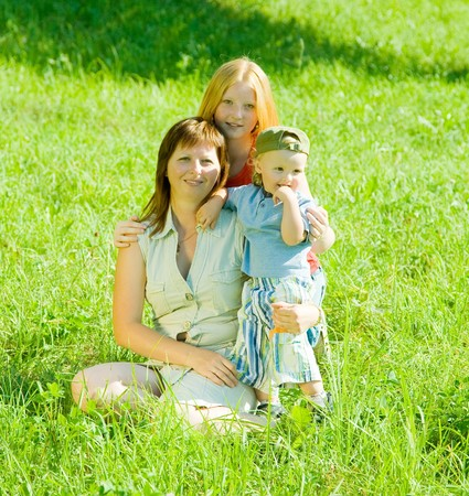 Happy mother with her children  sit in grass Stock Photo - 7375328