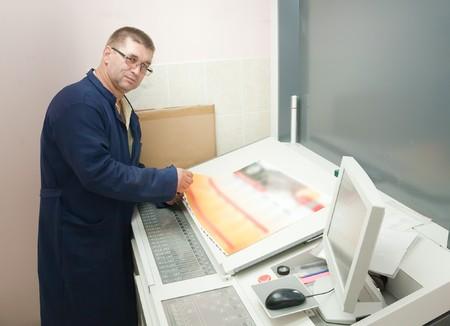 Printer checking a print run at table Stock Photo - 7394574