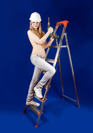 Topless woman  with drill on scaling-ladder over blue photo