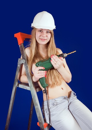 Topless girl  with drill on stepladder over blue photo