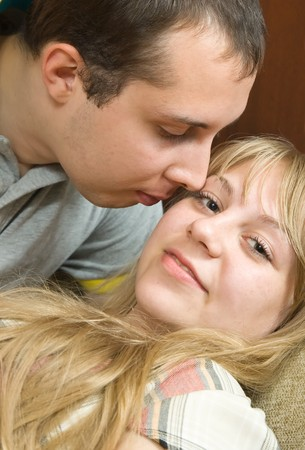 Young couple in love  on the couch kissing Stock Photo - 7521668