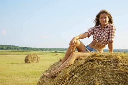Pretty girl in checked shirt resting on straw bale Stock Photo - 7521672