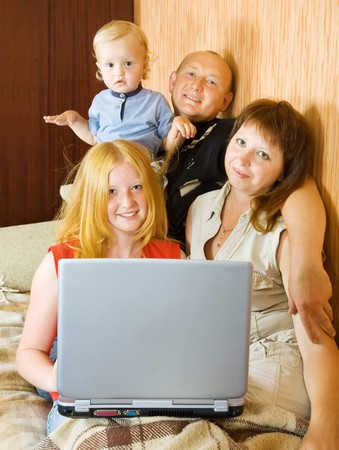 Happy young family using laptop at home photo