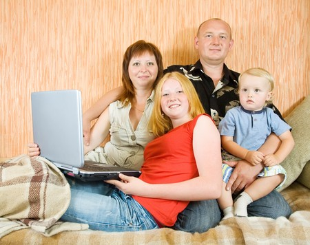 Young family shopping online in the living-room photo