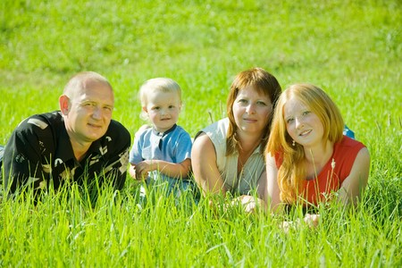 Happy family of 4 people lying on grass under summer sun photo