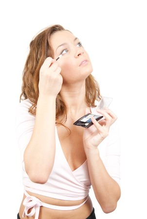 young woman putting make up on her face. Isolated over white photo