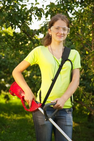Girl works with hand grass-cutter in garden photo