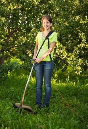trimmer: Girl works with cordless grass trimmer in garden