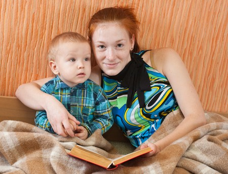 mother with her son reading book on sofa Stock Photo - 7420438
