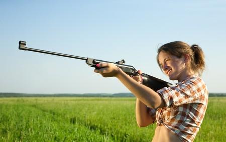 girl  aiming a pneumatic air against summer field photo