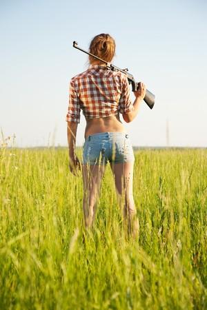 jeune fille avec air fusil contre champ  Banque d'images