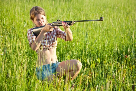 weapons: girl  aiming a pneumatic air rifle  in grass meadow