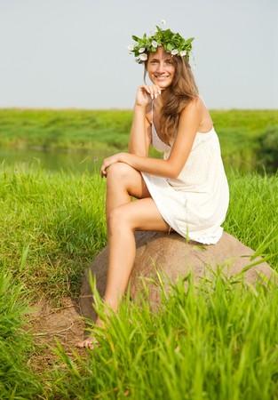 barfu�: H�bsches M�dchen in Blumen Kranz sitzt auf Feld Stein