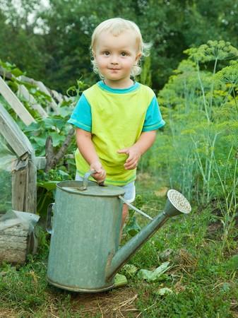 watering pot: baby boy with watering pot in summer garden