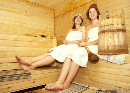 stive: girls in white sheet sits on bench in sauna Stock Photo