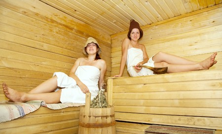 young women  sits on bench in  sauna photo