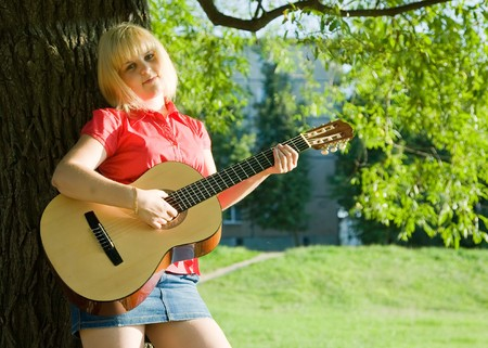 Teenager girl with guitar against green grass Stock Photo - 7449134
