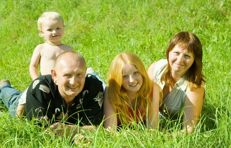 Happy family  from four posing on grass against nature photo