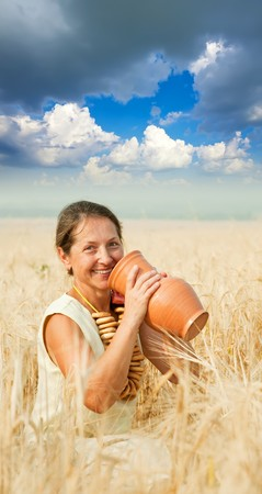 Woman in traditional clothes with jug at cereals field photo