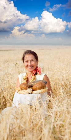 Woman with bread at cereals field in summer Stock Photo - 7465052