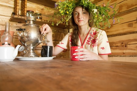 girl having tea from traditional russian samovar in  interior photo