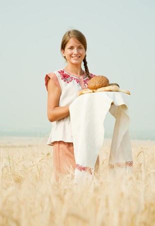 Girl in traditional clothes with bread  at rye field photo