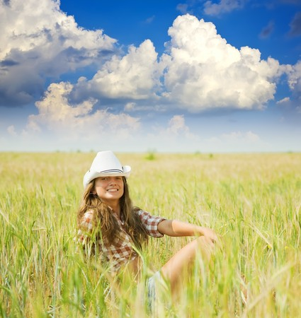 girl  in hat at cereals field in summer photo