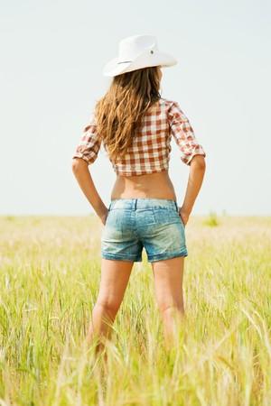 vaqueras: Chica permanente en el sombrero en el campo de cereales en verano  Foto de archivo