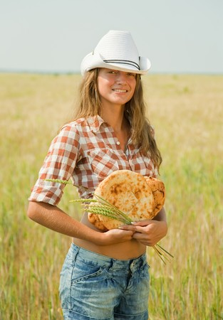 Young girl with bread at cereals field in summer Stock Photo - 7465083