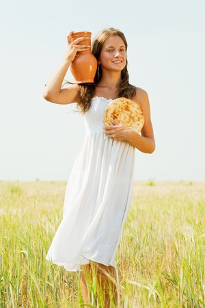 Young woman  with bread at cereals field in summer photo