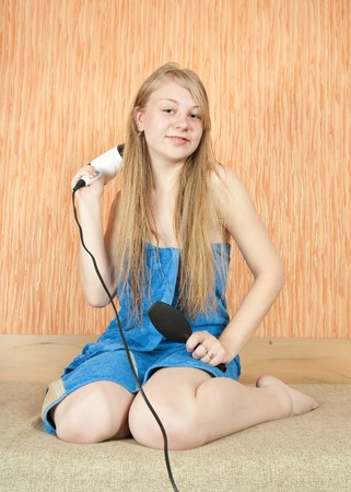 Girl dryes her long hair in home interior photo