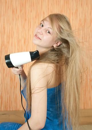 Blonde girl using hairdryer in home interior photo