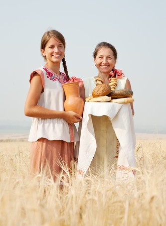 Women in traditional clothes with bread at cereals field Stock Photo - 7483952