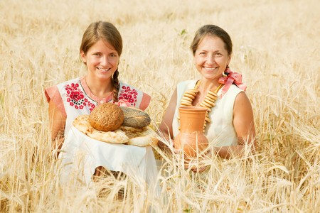 Women in traditional clothes with bread at cereals field photo
