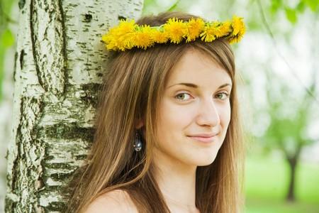 long-haired teen girl in chaplet near birch Stockfoto