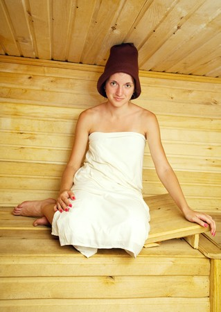 young girl sits on bench in  sauna photo