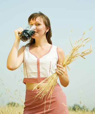 Girl  with beer and wheat ears  at cereals field Stock Photo - 7484302