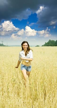 Running girl on wheat field in summer photo