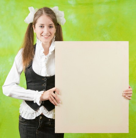 long-haired girl in school outfit  holding  blank canvas over green background photo